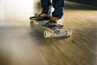 Businessman riding longboard on wooden floor - JOSF02231