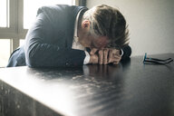 Mature businessman resting his head on the table - JOSF02237