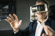 Mature businessman wearing VR glasses in office - JOSF02240
