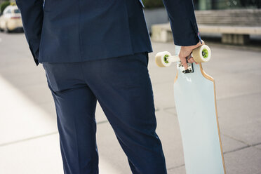 Businessman holding longboard outdoors - JOSF02246