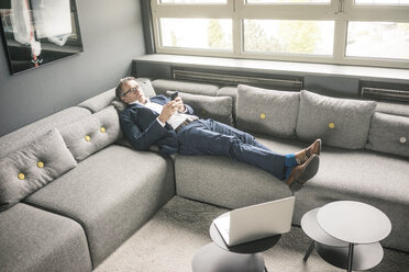 Mature businessman lying on couch using cell phone - JOSF02261