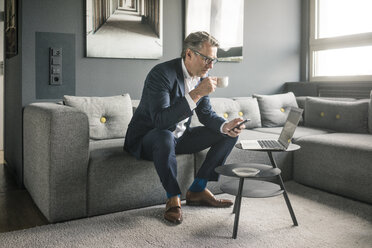 Mature businessman with cup of coffee and laptop using cell phone on couch - JOSF02264
