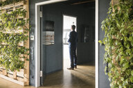 Mature businessman standing at a door in green office - JOSF02267