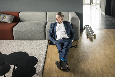 Mature businessman relaxing on the flooor next to longboard - JOSF02276
