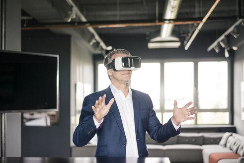 Mature businessman wearing VR glasses - JOSF02282