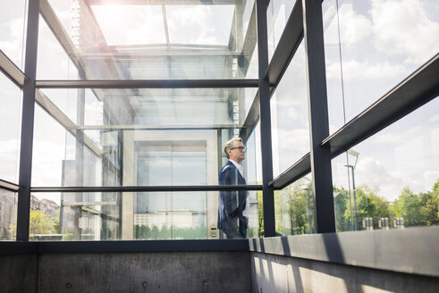Mature businessman at glass structure in the city looking around - JOSF02285