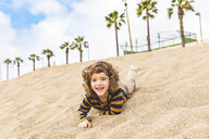 Spain, Barcelona, boy having fun in the sand on the beach - WPEF00361
