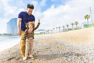 Spain, Barcelona, young boy with feet over his father on beach with pebbles - WPEF00364
