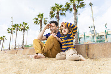 Spain, Barcelona, father and son sitting on the beach looking at distance - WPEF00370