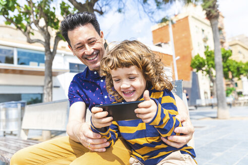 Spain, Barcelona, happy father and son with a smartphone sitting on bench - WPEF00379