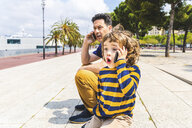Spain, Barcelona, father and son both with a smartphone - WPEF00382