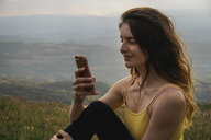 Spain, Barcelona, portrait of smiling young woman using cell phone on Montcau Mountain - AFVF00542