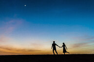Silhouetted view of romantic mid adult couple holding hands at dusk, Maspalomas, Gran Canaria, Canary Islands, Spain - CUF15121