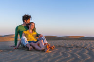 Romantic mid adult couple sitting on sand dunes at sunset, Maspalomas, Gran Canaria, Canary Islands, Spain - CUF15124