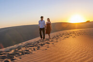 Romantic mid adult couple strolling on dunes at sunset, Maspalomas, Gran Canaria, Canary Islands, Spain - CUF15127