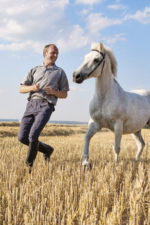 Male trainer running in front of white horse in field - CUF15142