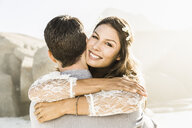 Portrait of woman hugging boyfriend on sunlit beach, Cape Town, South Africa - CUF15307