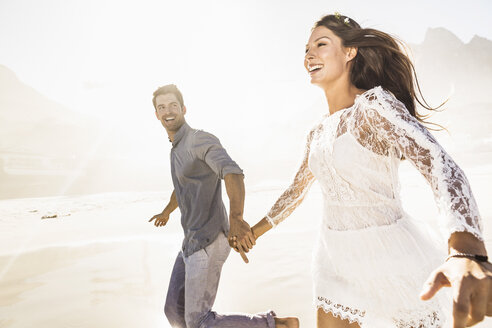 Couple running hand in hand on sunlit beach, Cape Town, South Africa - CUF15310