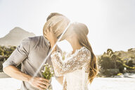 Romantic couple kissing on sunlit beach, Cape Town, South Africa - CUF15316