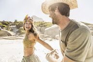Mid adult couple wearing straw hat and feather headdress running on beach, Cape Town, South Africa - CUF15328