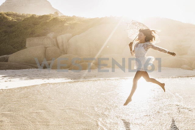 Woman jumping mid air with parasol on sunlit beach, Cape Town, South Africa - CUF15367