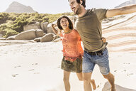 Couple holding up blanket running on beach, Cape Town, South Africa - CUF15376
