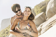 Couple wearing swimwear hugging on beach, Cape Town, South Africa - CUF15379