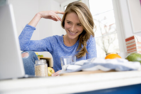 Happy woman sitting at kitchen table browsing laptop - CUF15400