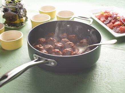Saucepan of steaming greek meatballs on table - CUF15523