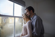 Mid adult couple gazing out through bedroom window - CUF15730