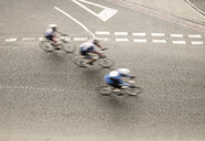 Overhead view of three cyclists speeding on urban road in racing cycle race - CUF15943