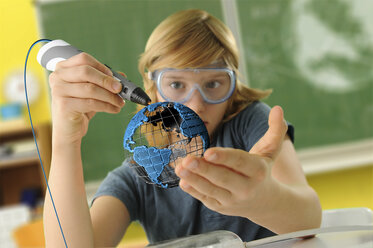 Boy with digital pen and 3D model of globe in classroom - CUF16093