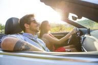 Young couple driving on sunlit rural road in convertible, Majorca, Spain - CUF16099