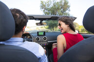 Young couple laughing whilst driving on rural road in convertible, Majorca, Spain - CUF16102