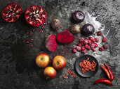 Overhead view of halved red fruit and vegetables on dark background - CUF16120