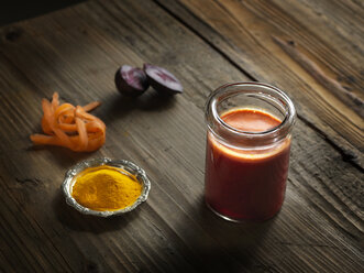 High angle view of orange raw juice in a jar with beetroot, turmeric and grated carrot on wood grain pattern background - CUF16126