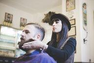 Female barber trimming man's beard in shop - CUF16165
