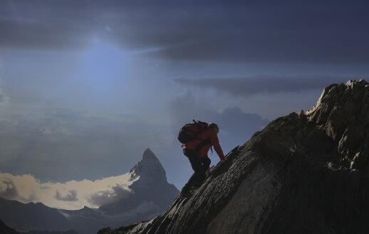 Senior male climber climbing rock face near Matterhorn, Canton Wallis, Switzerland - CUF16294