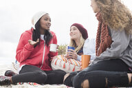Three young women chatting on beach picnic, Western Cape, South Africa - CUF16345