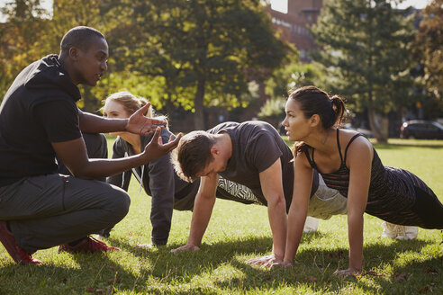 Personal trainer instructing man and women doing push ups in park - CUF16369