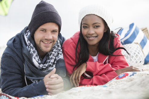 Portrait of young couple lying on picnic blanket at beach, Western Cape, South Africa - CUF16375