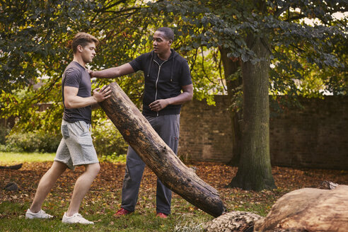 Young man with personal trainer lifting tree trunk in park - CUF16378