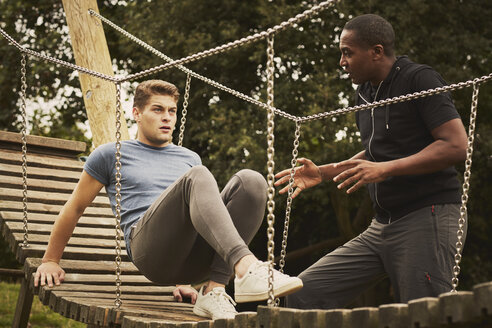 Personal trainer instructing man training on playground equipment in park - CUF16384