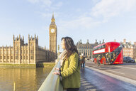 Side view of young woman on Westminster bridge, looking away, Thames river, London, UK - CUF16489