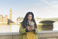 Young woman in front of Westminster bridge and Big Ben looking down using smartphone, Thames river, London, UK - CUF16492