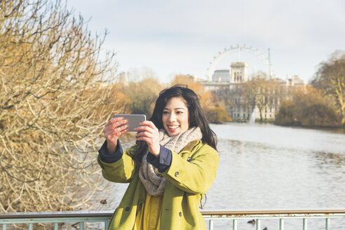 Young woman in St James's Park using smartphone to take selfie, smiling, London, UK - CUF16501