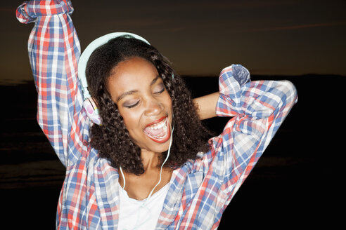 Young woman wearing headphones arm raised, eyes closed open mouthed smiling - CUF16513