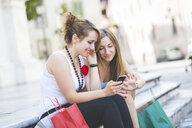 Girlfriends using smartphone on steps - CUF16564