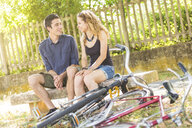 Young couple chatting on park bench, bicycles in foreground - CUF16570