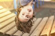 Girl in playground hanging upside down looking at camera sticking out tongue - CUF16573